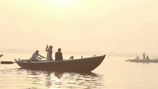 People in boats sailing down the river Ganges at sunset.