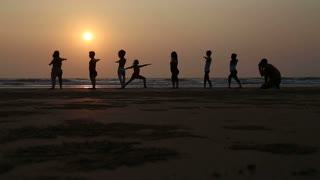 People stretching at a sandy beach in Goa at sunset, with man photographing.