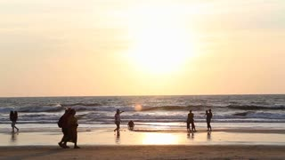 People walking down the sandy beach at sunset.