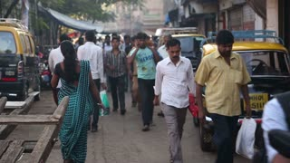 People walking through a busy street in Mumbai.