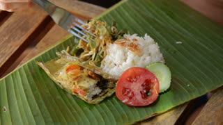 Person eating asian food off a banana leaf with fork