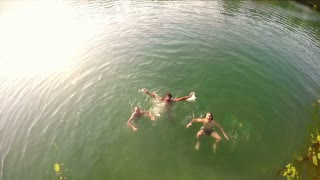 Person jumping into river, friends looking and laughing, graded, in slow motion