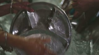 Person washing silver plate at public kitchen in Amritsar, closeup.