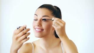 Portrait of beautiful woman putting on mascara on isolated white background