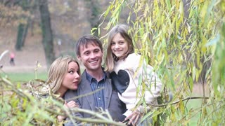 Portrait of beautiful young family in park on nice autumn day, smiling and enjoying