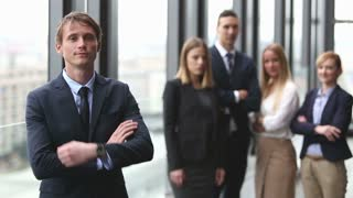 Portrait of handsome young businessman smiling, colleagues in background