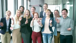 Portrait of happy business and advertising team, laughing and clapping, slow motion, graded
