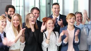 Portrait of happy business people clapping, slow motion