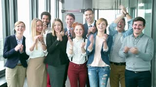 Portrait of happy business people, laughing and clapping in office, graded