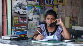 Portrait of Indian woman talking on the phone by a counter.