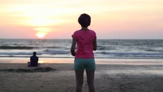 Portrait of woman watching the ocean on sandy beach at sunset.