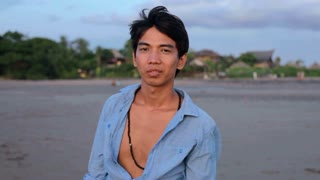 Portrait of young Asian man standing on beach at sunset in Bali, Indonesia.