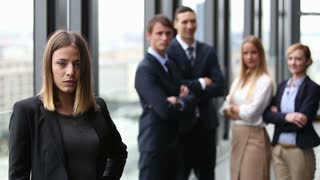 Portrait of young beautiful businesswoman smiling, colleagues in background