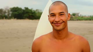 Portrait of young smiling Asian surfer on beach with his surfboard