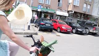 Pretty blonde girl riding bike on the street, adjusting hat