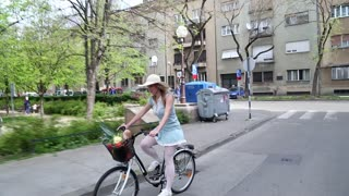 Pretty blonde girl riding bike on the street, holding hat