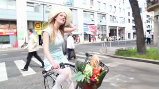 Pretty blonde girl riding bike on the street