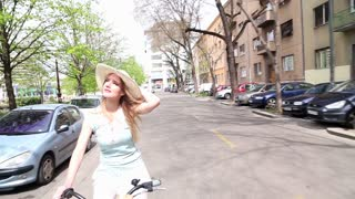 Pretty blonde girl riding bike on the street