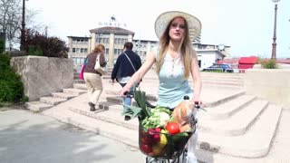 Pretty blonde girl riding bike with basket full of fruits and vegetables