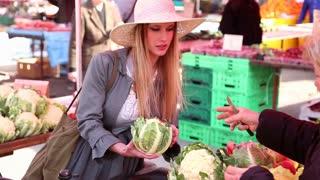 Pretty girl holding cauliflower in the market