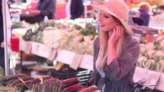 Pretty girl picking vegetables at the market