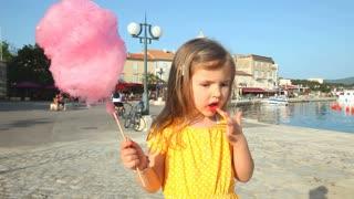 Pretty little girl eating candy floss