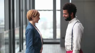 Profile of beautiful female creative director and male advertising executive shaking hands, slow motion