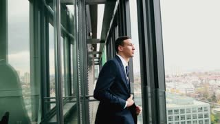 Profile of handsome businessman standing by the window with city view, graded