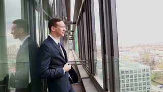 Profile of handsome smiling businessman standing by the window with city view