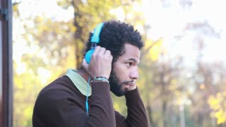 Profile of man putting on headphones and listening to music in nature
