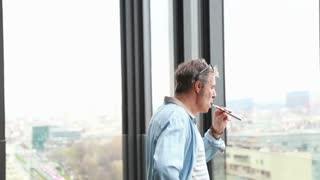 Profile of middle age creative director standing by window, smoking electronic cigarette