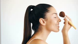Profile of smiling woman applying powder on her face