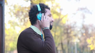 Profile of young man listening to music with headphones, enjoying in nature