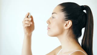 Profile of young woman putting on mascara