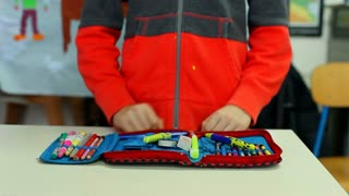 Pupil showing off his pencil case content in school classroom