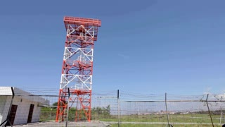 Red and white metal radar tower in airport area