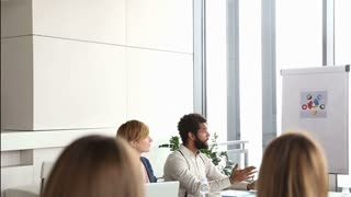 Red hair female advertising executive discussing with colleagues on a meeting in conference room