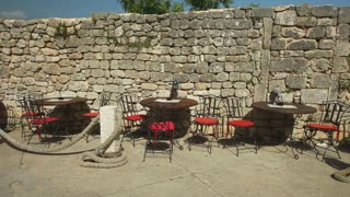 Restaurant with tables and chairs outside near old stone wall