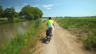 Retired couple cycling beside river on holiday