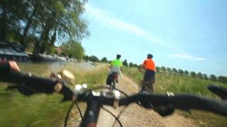 Retired couple cycling beside river on holidays