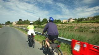 Retired couple cycling on road beside river on holidays