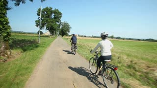Retired couple cycling on road in village in France