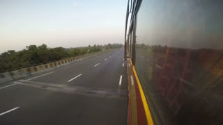 Road view with vehicles passing from bus window during ride, time lapse.