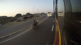 Road view with vehicles passing from bus window during ride.