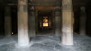 Room with columns and Buddha statue inside of Aurangabad caves.