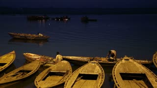 Sailors on boats in bay of Ganges river in night time.