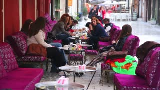 SARAJEVO, BOSNIA - MARCH 2014: People sitting and having coffee at market on the rainy day. Bosnia is well known as a country of drinking coffee culture.
