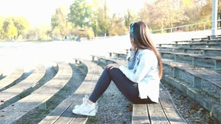 Side view of attractive brunette woman listening to music on headphones, sitting on bench at park, graded