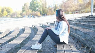 Side view of attractive brunette woman listening to music on headphones, sitting on bench at park