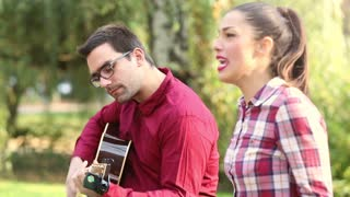Side view of beautiful young couple playing guitar and singing in park, graded